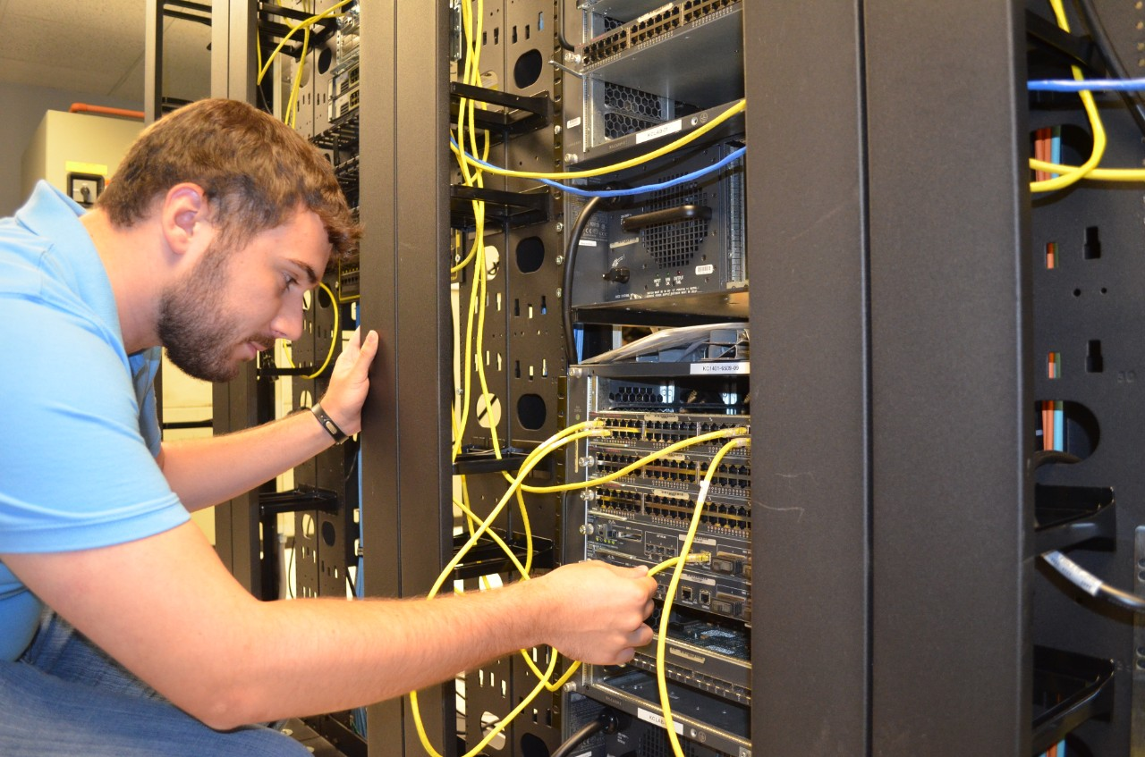 man looking at computer network wires